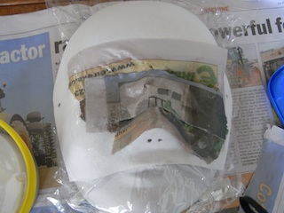 Cover the eyes with paper, unless you want to use the eyeholes. Once the paper mache is dry you can drill eye holes.