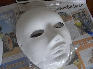 I use cardboard masks. Place your mask over another one in plastic, because adding wet paper mache makes it flop out of shape.
